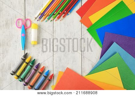 Composition with color paper, pencils and crayons on wooden background