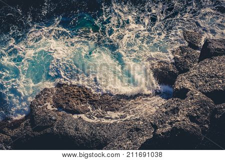 Waves crashing breaking on the rocks. Drone aerial sea surface view. Aerial view with drone on the seashore where the waves crashing on the rocks rocky. Foam and splashes. Deep, intense colors.