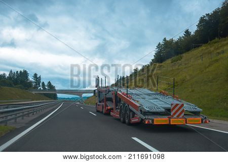 Semi truck with empty car carrier trailer on highway road