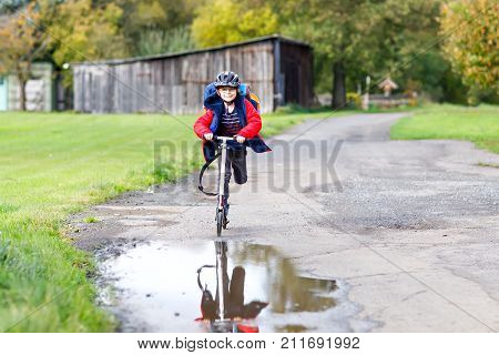 cute little school kid boy riding on push scooter on the way to or from school. Schoolboy of 7 years driving through rain puddle. funny happy child in colorful fashion clothes and with helmet