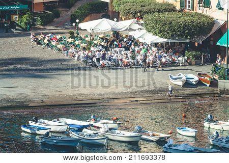 PORTOFINO, ITALY. October 20, 2017: Portofino in Italy, sea and coast. Piazza (Square) Martire dell'Olivetta, tourists and boats in the small marina port.