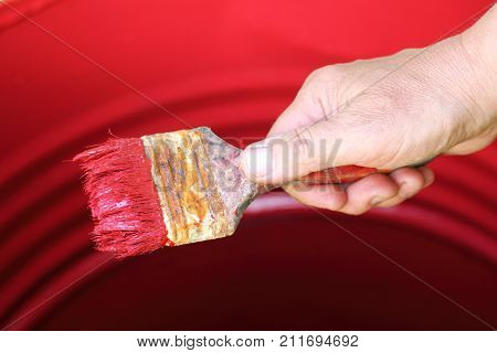old brush in the hand of the painter paints the metal surface with red paint / work on restoring the barrel