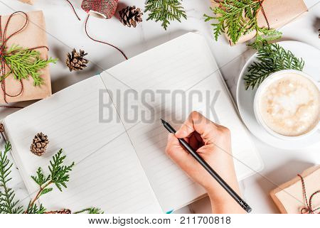 Woman write wishes or to do list in notebook coffee mug Christmas gift or present box decorated with christmas tree branches pine cones red berries on white marble table copy space top view