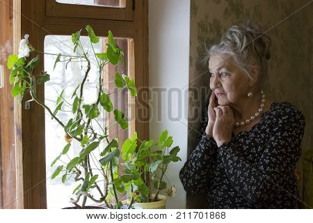 Old beautiful woman at the window.A very old woman. An eighty-year-old woman. Studio portrait of an old woman.Lonely old age. Nursing home