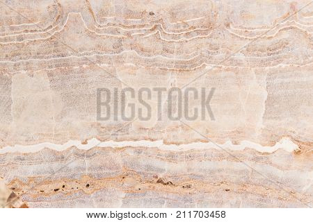 Lightened slices marble onyx. Horizontal image. Warm colors. Beautiful close up background. Pink onyx marble texture. Ideal for sites, banners, brochures, design