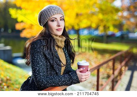 Portrait Of Young Woman With Cup Of Coffee In Yellow Autumn Park
