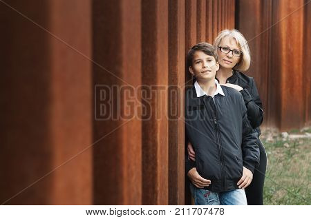 Good-looking single-parent mom and teen son in the park. Photo with copy space. Cohesion friendship and family relations.