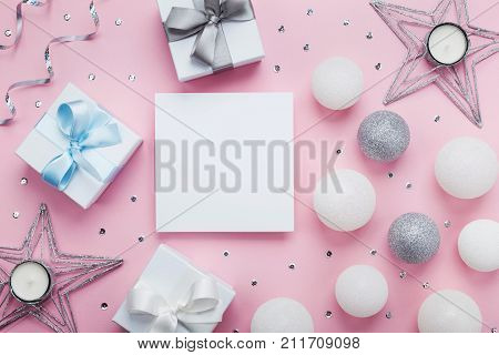 Empty paper blank gift box and decoration on pink table top view. Christmas mockup or greeting card. Flat lay.