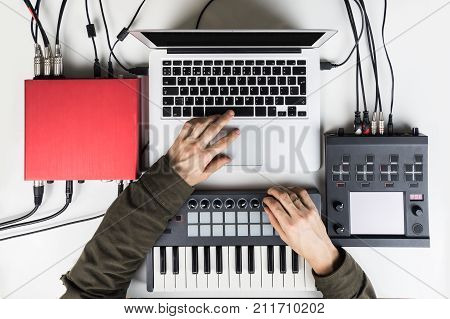 Producing and mixing modern style beats music, beat making and arranging audio content with software controllers and digital effects processors. Recording electronic music track with portable midi keyboard on laptop computer in home studio