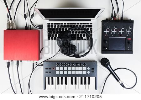Portable and compact music home studio for electronic and beat music production. Top view of modern music recording set up with professional headphones software controllers digital effect processors and interfaces and laptop computer
