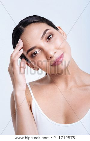 Pleasant smile. Smiling dark-eyed woman tilting her head and touching her forehead with her hand while smiling at the camera