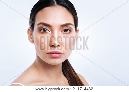 Ethereal beauty. The portrait of a gorgeous dark-haired young woman with a swarthy complexion having a pony tail, looking at the camera while posing against a white background