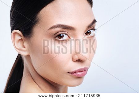 Mesmerizing eyes. The close up of a gorgeous young brunette standing half-turned and looking into the camera intently while posing against a white background