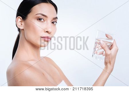 Hydration is crucial. Beautiful dark-haired young woman holding a glass of water and looking at the camera while being wrapped in a towel, posing against a white background