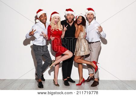 Portrait of a cheery happy multiracial group of friends celebrating New Year together while posing and showing peace gesture isolated over white background