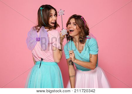 Two cheerful young girls dressed like fairies with wings holding magic wands while looking at camera over shoulder isolated over pink background