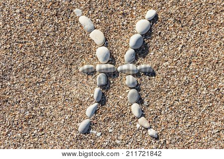 Astrological Sign of the Zodiac Pisces February 19 - March 20 laid out by sea pebbles on the sandy shore. High resolution. Close-up. Top view.