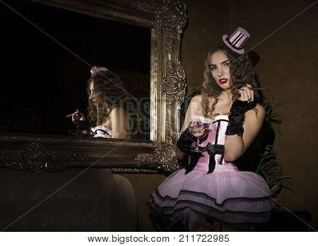 Sexy cabaret woman in corset posing near mirror. Burlesque lingerie in fashion interior. poster