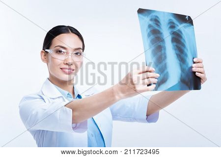 Studying thoroughly. Beautiful young woman in safety glasses holding X-ray examination results, ready to study them, while smiling at the camera