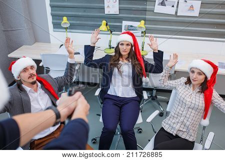 Close-up of a hand of a robber with a gun aimed at office workers wearing santa hats. Employees sitting in armchairs raised their hands up. The concept of business, finances, robbery.