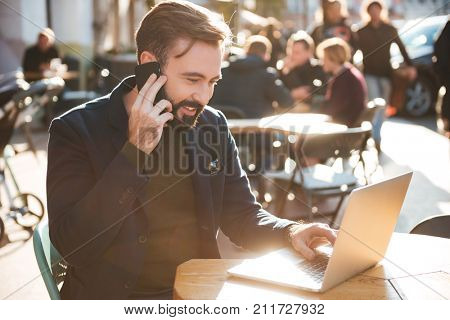 Portrait of a smiling stylish man working on laptop computer while sitting at the cafe outdoors and talking on mobile phone
