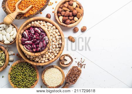 Vegan protein source. Legumes - lentils chickpeas beans green mung bean. seeds and nuts on white background. Top view copy space.