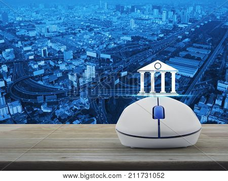 Bank icon with wireless computer mouse on wooden table over city tower street and expressway Business banking online concept
