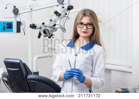 Portrait Of Young Beautiful Female Dentist Holding Dental Tools At The Morden Dental Office. Doctor
