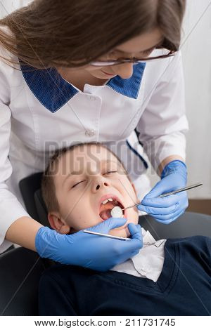 Female Dentist Examines The Teeth Of The Patient Child. Child Mouth Wide Open In The Dentist's Chair