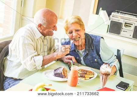 Happy seniors couple eating pancakes in a bar restaurant - Retired people having fun enjoying lunch together - Concept of elderly retired person moments - Vintage filter - Soft focus on male face