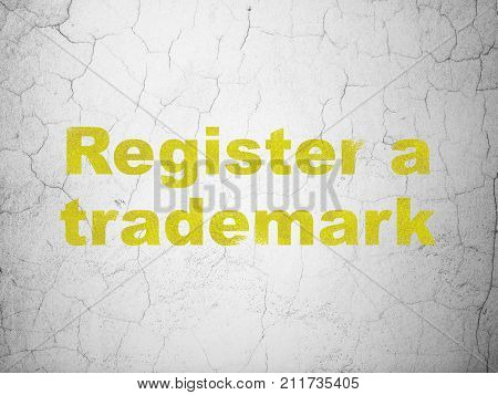 Law concept: Yellow Register A Trademark on textured concrete wall background