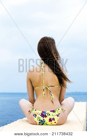Relaxing young woman on pier at the sea in summer day. Skinny girl in swimsuits posing near sea.