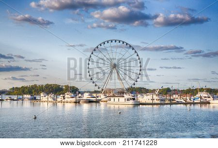 September 10 2017 Oxen Hill Maryland USA: Boats dcked on the national waterfront sit in front of the pier and ferris wheeel in late summer.