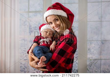 Young Mother, Holding Her Newborh Baby Boy, Infant With Santa Hat