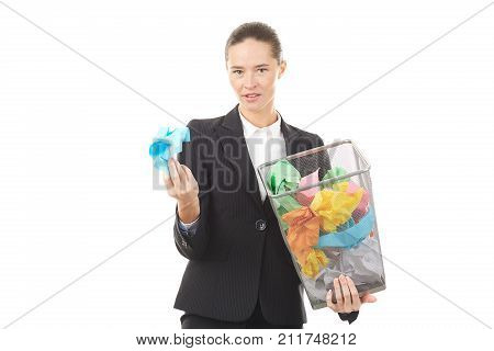 Portrait of female office worker holding basket with crumpled papers