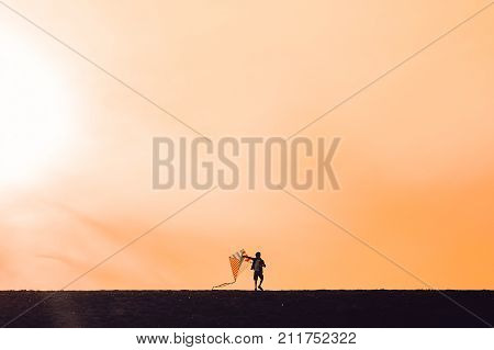 boy launching a kite. silhouette of a child with a kite in hands on a sunset background. Happy time of childhood. the wind of change. The concept of future. Copy space for your text