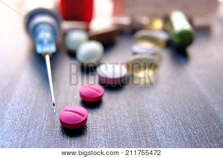 Medicine pills or capsules with syringe on white background. Drug prescription for treatment medication. Pharmaceutical medicament, cure in container for health. Antibiotic, painkiller or narcotic