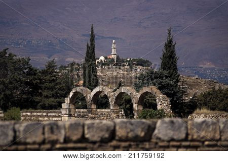View to a old mosque on a hill from the Great Palace of Umayyad Palace with blue sky and mountainrange in the background at Anjar in Lebanon.