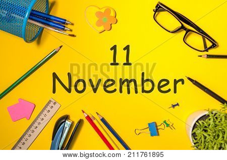 November 11th. Day 11 of last autumn month, calendar on yellow background with office supplies. Business theme.