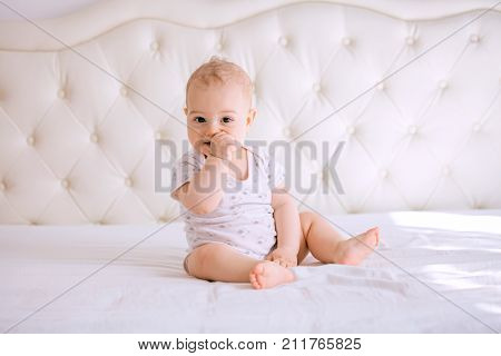 Adorable baby boy in white sunny bedroom. Newborn child relaxing in bed. Nursery for young children. Textile and bedding for kids. Family morning at home. Nursery for young children.
