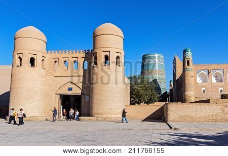 KHIVA, UZBEKISTAN - SEPTEMBER 15, 2013: Unidentified people in front of twin-turreted Gate with of Unfinished Kalta Minor Minaret in background - Khiva, Uzbekistan
