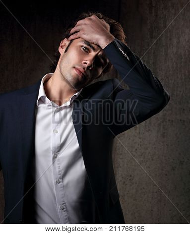 Charismatic Handsome Male Model Posing In Blue Fashion Suit And White Style Shirt Looking On Dark Sh