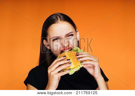 annoyed girl eating a burger in her hands