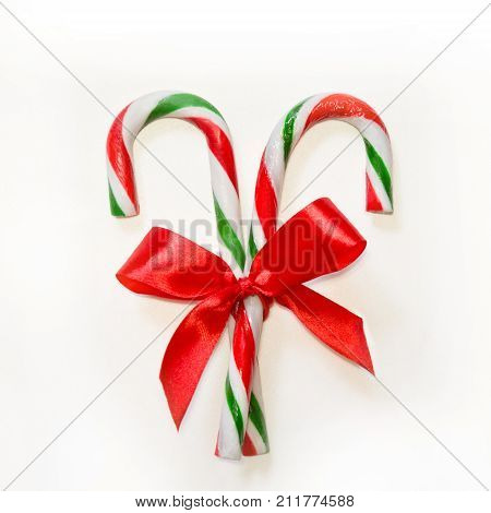 Two Candy Canes With Red Bow On White Background.
