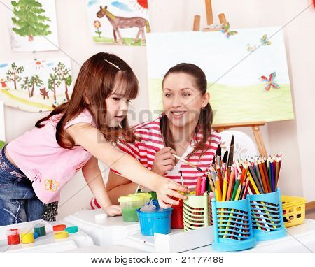 Child with teacher draw paints in play room. Preschool. poster