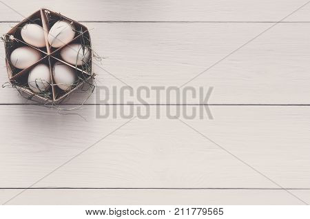 Thin wood box with six eggs on white wooden background, copy space. Top view on kitchen table with natural organic cooking ingredients.