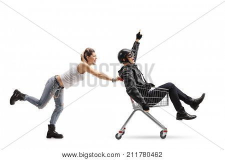 Punk girl pushing a shopping cart with a biker riding inside and pointing up isolated on white background