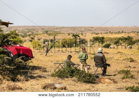 Family of father and kids on African safari vacation enjoying bush view