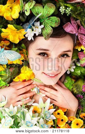 Beautiful girl with butterfly and flower on green grass. Outdoor.
