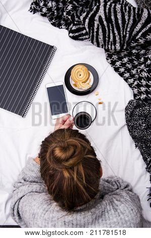 young trendy woman lying in the bed and drinking morning coffee and eat some pie. Life style concept